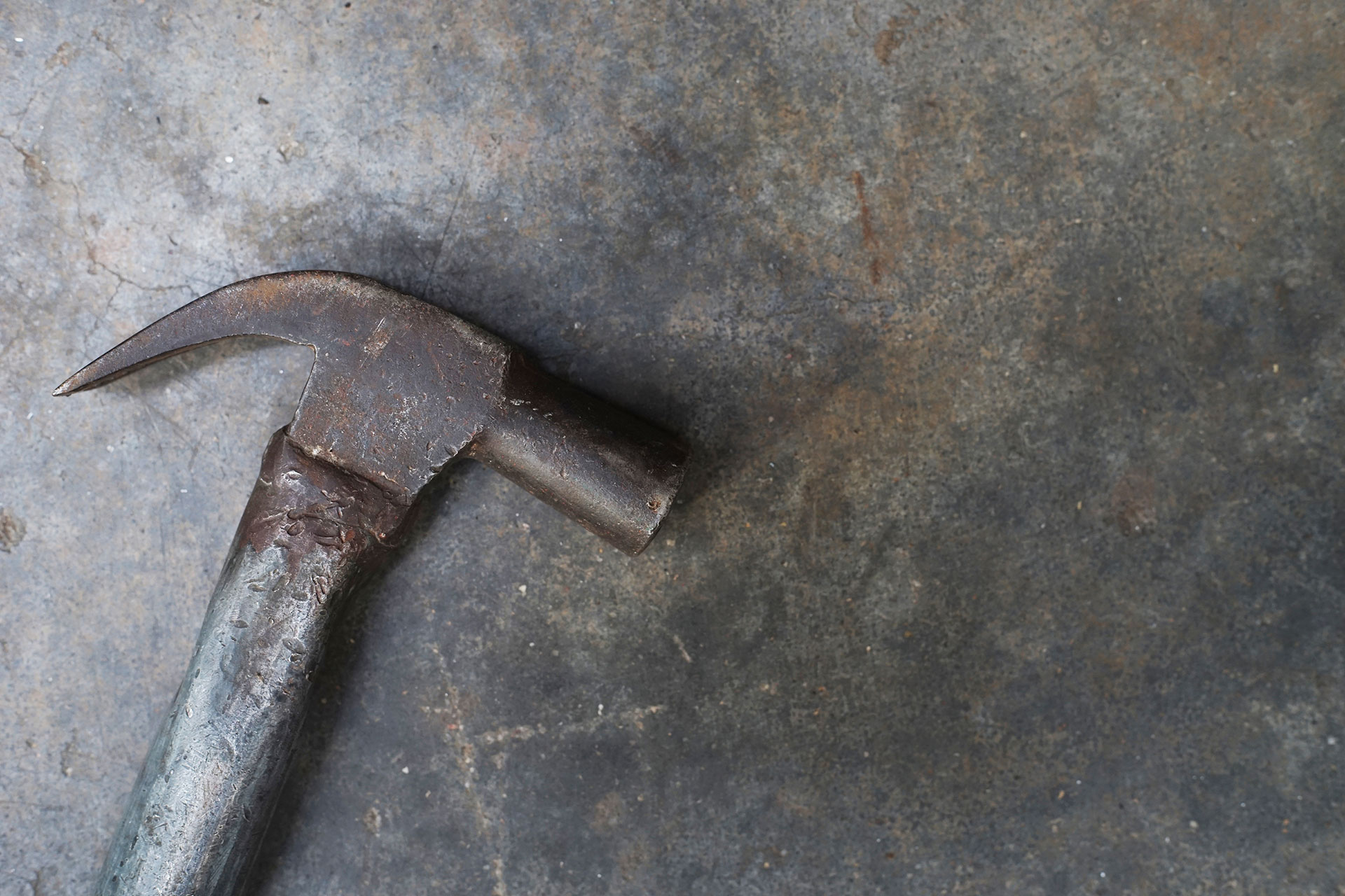 close-up-hammer-on-grunge-cement-background-000084531939_Full